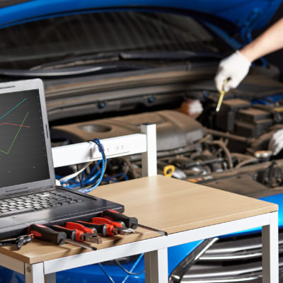 Equipment for electirc car testing with laptop. Diagnostic errors of modern car closeup.